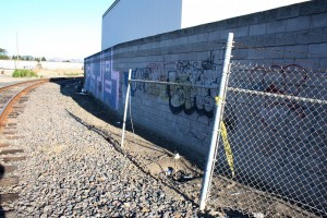 Weathered police tape still clings to a chain-link fence more than one month after it roped off the scene of a homicide.