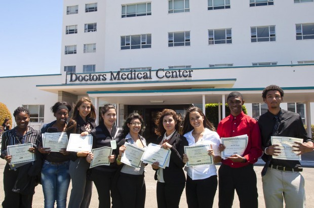 Richmond students pose with their graduation certificates outside Doctors Medical Center. From left to right: Keyannie Norford, Kristen Mason, Pearla Ponce, Brenda Valadez, Jessica Maciel, Nancy Barbar, Selena Castro, Alfreddi Beulah, Andre Ernest. (Photo by Tyler Orsburn)