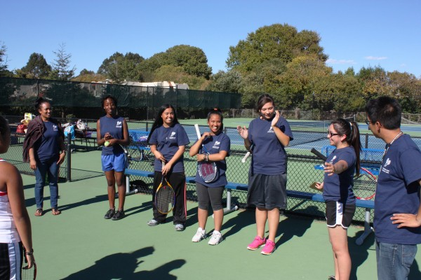 "The Richmond High School girls' tennis team before its match against Salesian High School. From left to right: team mom Deserel Afable, Evelina Stewart, Josephine Huynh, Elizabeth ""Ebey"" Alonzo, team captain Preciosa Roberts, Celeste Ramirez and coach Tyler Chuck. (Photo by Kevin N. Hume)"