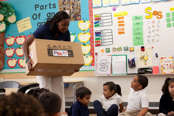 Leah Casey, community engagement specialist for Chevron Richmond, delivers a box of school supplies to a Ford Elementary School class. (Photo by: Sara Lafleur-Vetter)