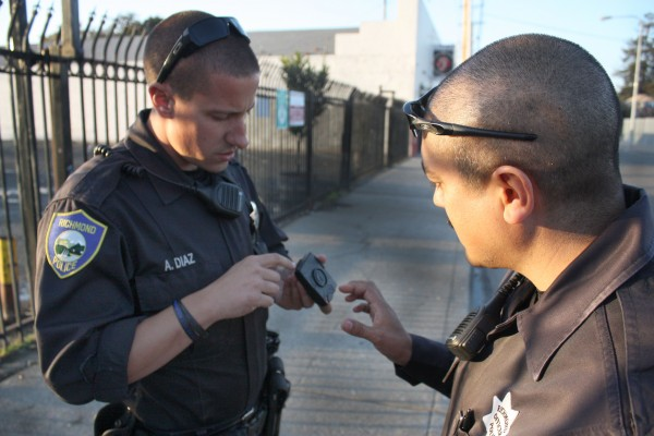 Richmond Police Officer Anthony Diaz, left, looks at fellow officer Phillip Sanchez's body camera. Sanchez, right, was one of four officers selected to test body cameras for the department before they issue them to all patrol officers. Photo is from an earlier story on police body cameras last year. (Photo by: Kevin N. Hume)