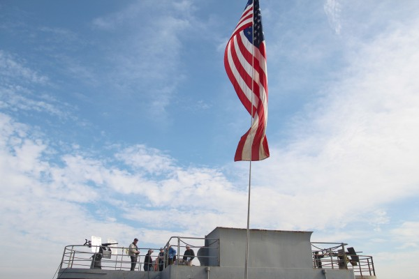 Veteran's Day observers gather on an SS Red Oak Victory gun deck during the celebration at the Port of Richmond. (Photo by: Kevin N. Hume)
