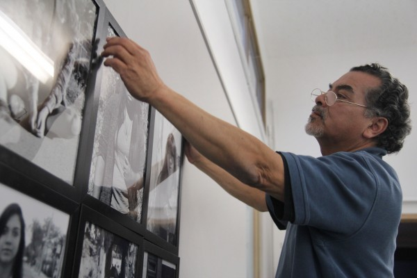 Anthony Torres, exhibitions director and curator for the Richmond Art Center, hangs portraits of Richmond teenagers taken by young photojournalists as part of the American Teenager Project. The exhibition runs at the art center from Jan. 11 through March 7. (Photo by: Kevin N. Hume)