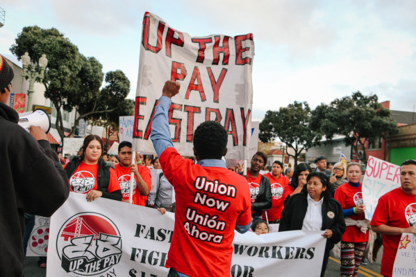 Claude Joseph, an organizer with the East Bay Organizing Committee, leads a march down International Blvd. in Oakland on Dec. 4, 2014. Workers are calling for a $15 base wage and the right to unionize. (Photo by Bonnie Chan)