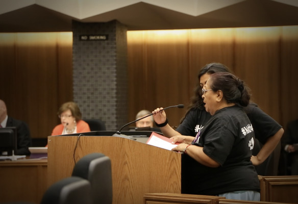 Edith Pastrano listens to undocumented resident Rosa Maria Arriaga so she can translate Rosa's story for the Board of Supervisors. (Photo by Manjula Varghese)
