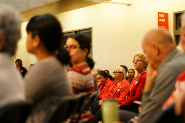 Three nurses, clad in CNA's characteristic red, listened to the panel speakers from the audience. Photo by Margaret Katcher