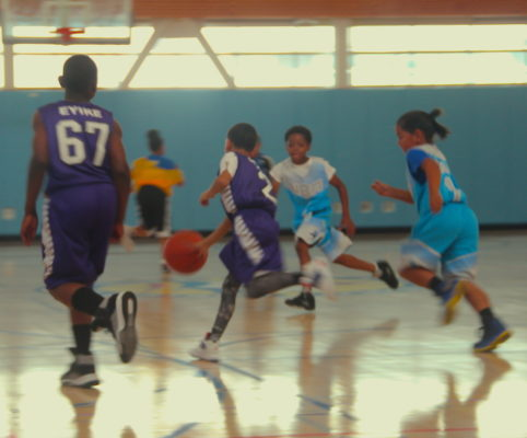 A young boy dribbles the ball across the court in a fierce competition. Photo by Angeline Bernabe.