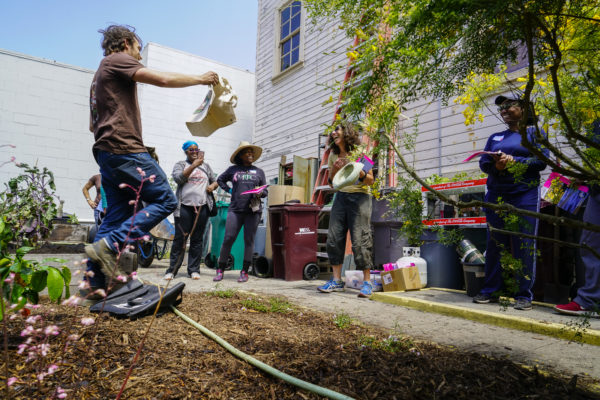 Volunteers laugh and smile as Trevor Probert raffles a StopWaste bag at the Memorial Tabernacle Church for a lawn party to restore the church's garden on Saturday, May 6, 2017. (Yesica Prado/Oakland North)