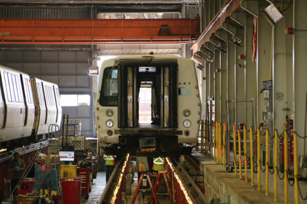 A crew of repair shop workers inspect the underside of a BART car. Performing routine maintenance is a daily part of mechanics' job at the Richmond yard.