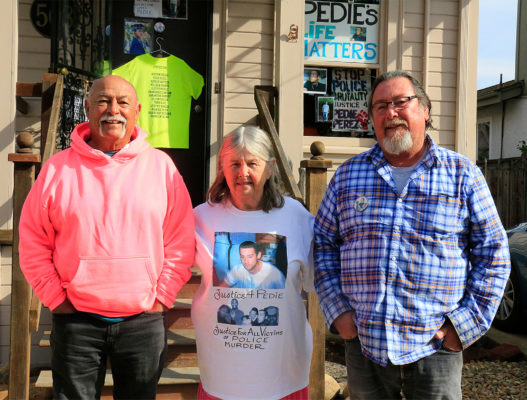 Rick Perez Sr., Pat Perez, and Rick Perez Jr. stand outside of Richard and Pat's home, which is decorated with signs commemorating Pedie Perez.